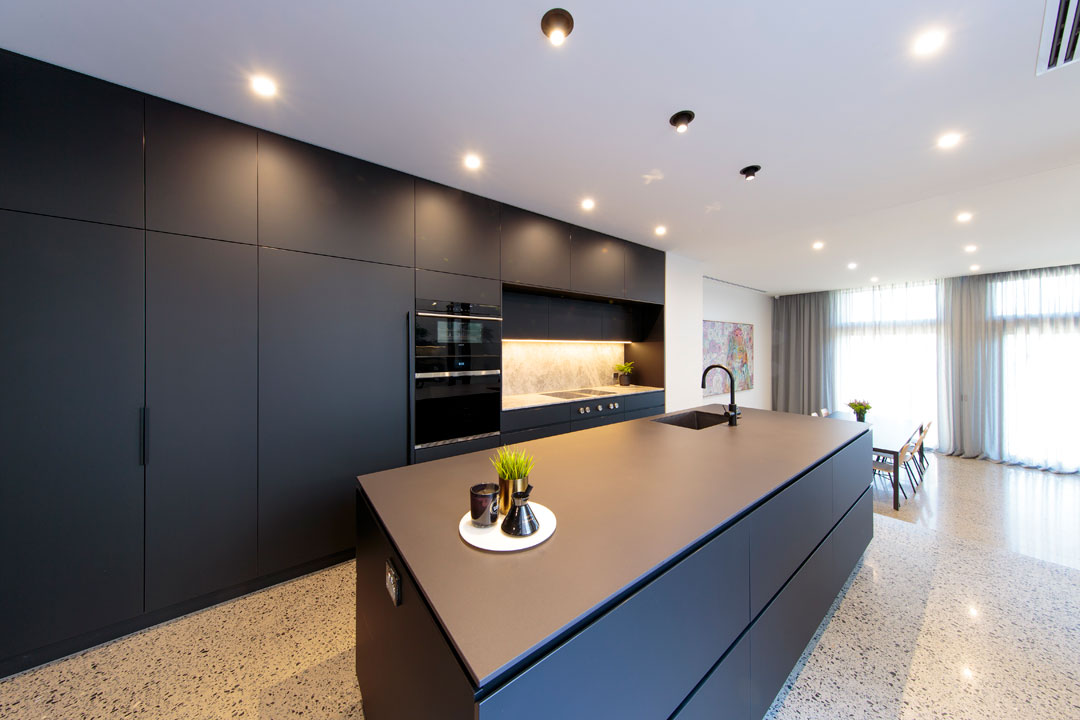 MTR Designer Cabinets kitchen with black cabinetry and polished concrete floors